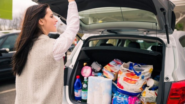A woman prepares to close the door on a chest full of groceries.