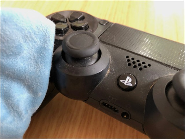 A cloth wiping a DualShock 4 controller.