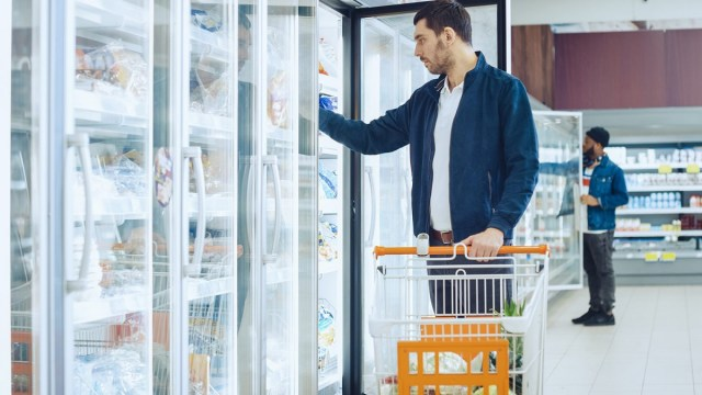Man retrieving items from a grocery freezer.