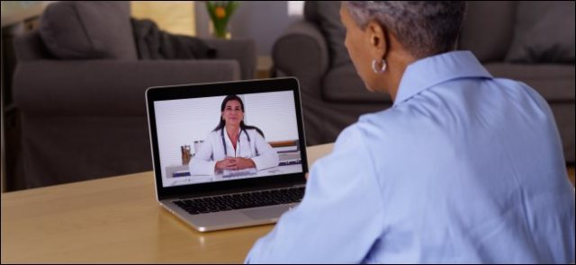 Older woman talks to doctor on laptop