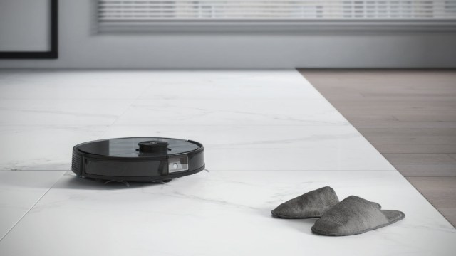 An Ecovacs vaccumm robot avoiding a pair of slippers.