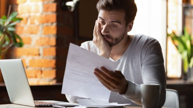 Man looking at a letter, trying to determine if it is a scam.