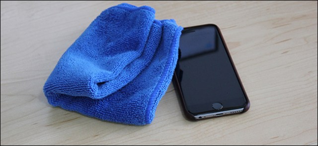 A blue microfiber cloth sitting next to an iPhone.