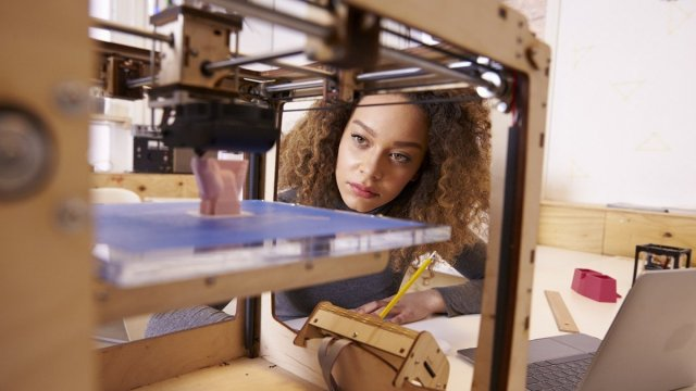 A woman uses a 3D printer to create a plastic model.
