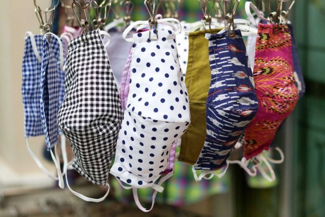 The cloth masks are hung on drying on a small drying rack.