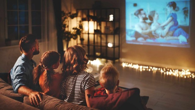 Family watching a film projected on the wall of their living room.