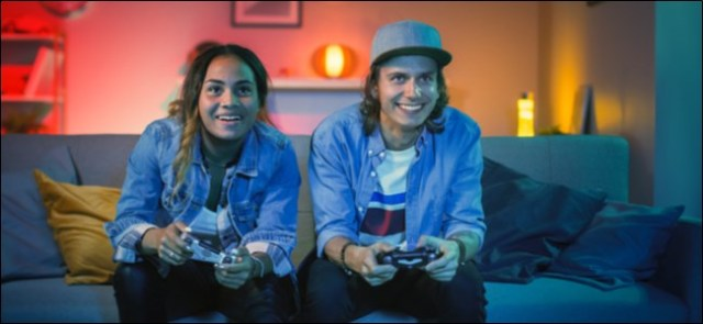 A man and a woman sitting on a sofa playing a video game.