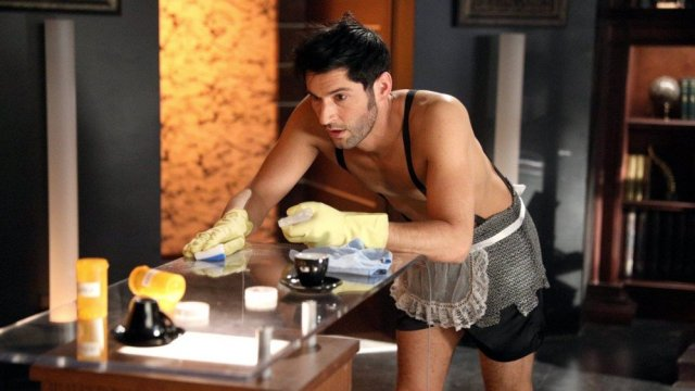 Lucifer in French maid clothes, cleaning a counter stocked with drugs.
