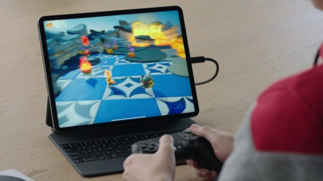 A player using a DualShock 4 controller with the iPad Pro.