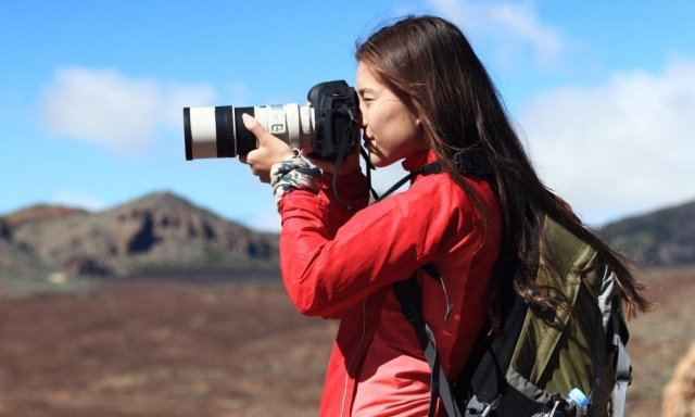 Woman with backpack using dslr camera and zoom lens