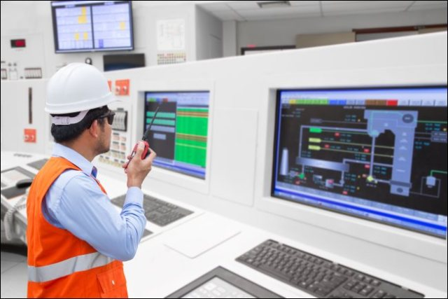 An electrical engineer in front of computers in the control room of a thermal power plant.