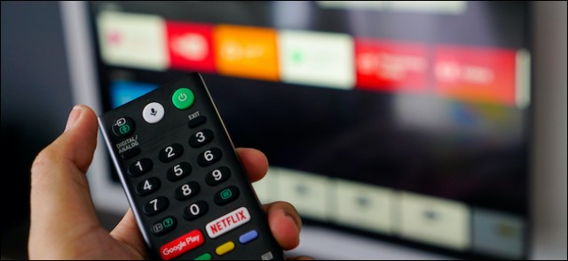 Someone who holds an Android TV remote control.