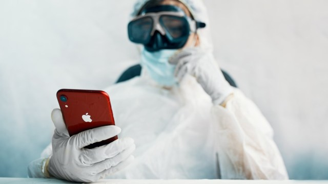 A person wearing a biohazard suit trying to unlock their iPhone.