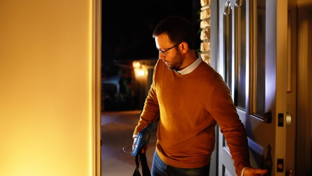 A man walks into a well-lit house.