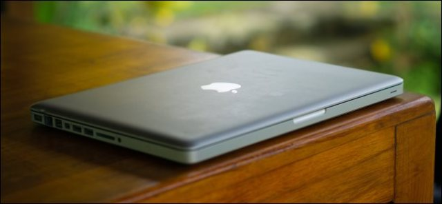 An old, thick MacBook Pro sitting on a wooden desk.