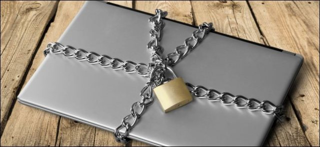 A laptop closed with a chain and a padlock.