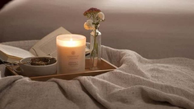 The Chesapeake Bay peace + tranquility candle lit on a flowery platter.