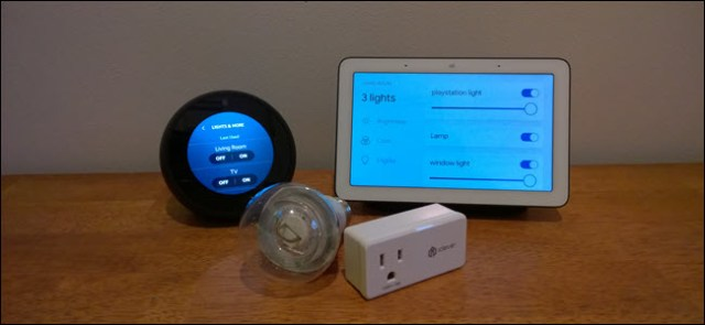 An Echo Spot, Google Home, a smart bulb and a smart plug on a wooden surface.