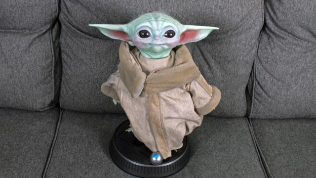 A replica of Baby Yoda looking at the camera.