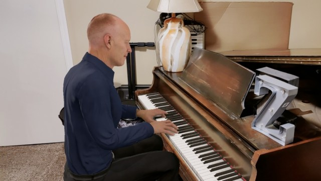 A CGI Jon Schmidt from the Piano guys super imposed on a real piano.