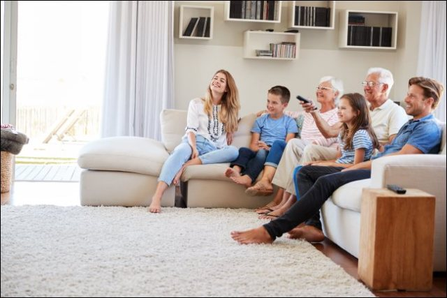 A family sitting on a sofa watching television.