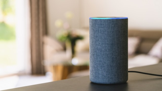Voice activated smart speaker on table in comfortable bedroom
