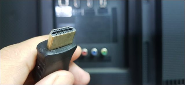 Hand holding an HDMI cable.