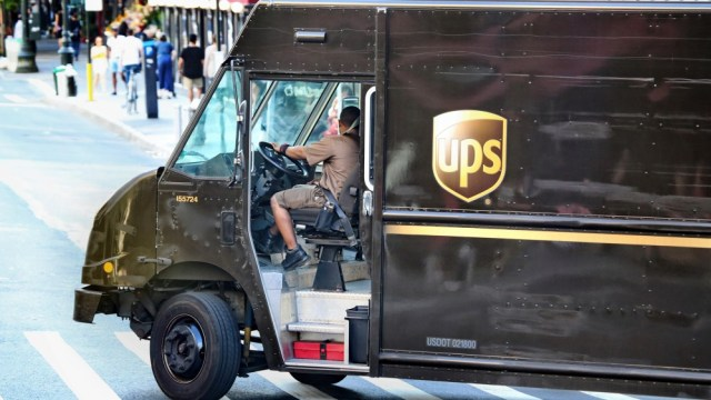 A UPS truck turning in a street.