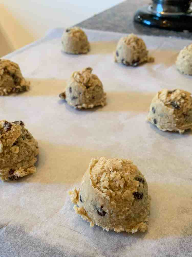 A batch of oatmeal raisin cookies, scooped on a tray and ready to be baked.