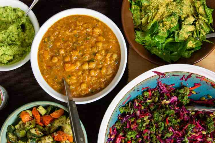 Dishes filled with toppings at a baked potato party. Moroccan chickpea stew, winter slaw, spinach salad, and guacamole.