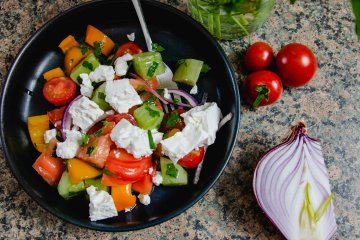 Bulgarian Shopska Salad in a blue bowl with some red onion an cherry tomatoes on the side
