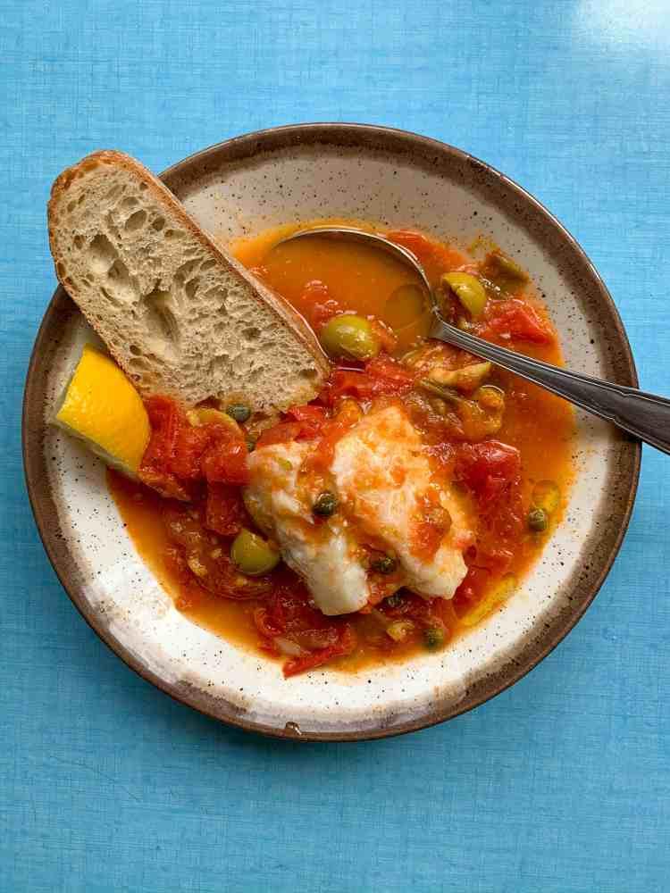 a bowl of tomato caper olive fish stew with bread