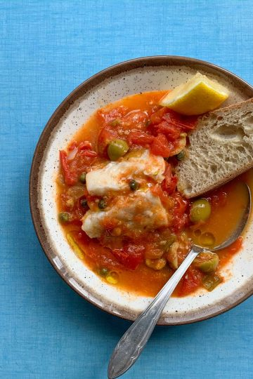 a bowl of summer fish stew on a blue table