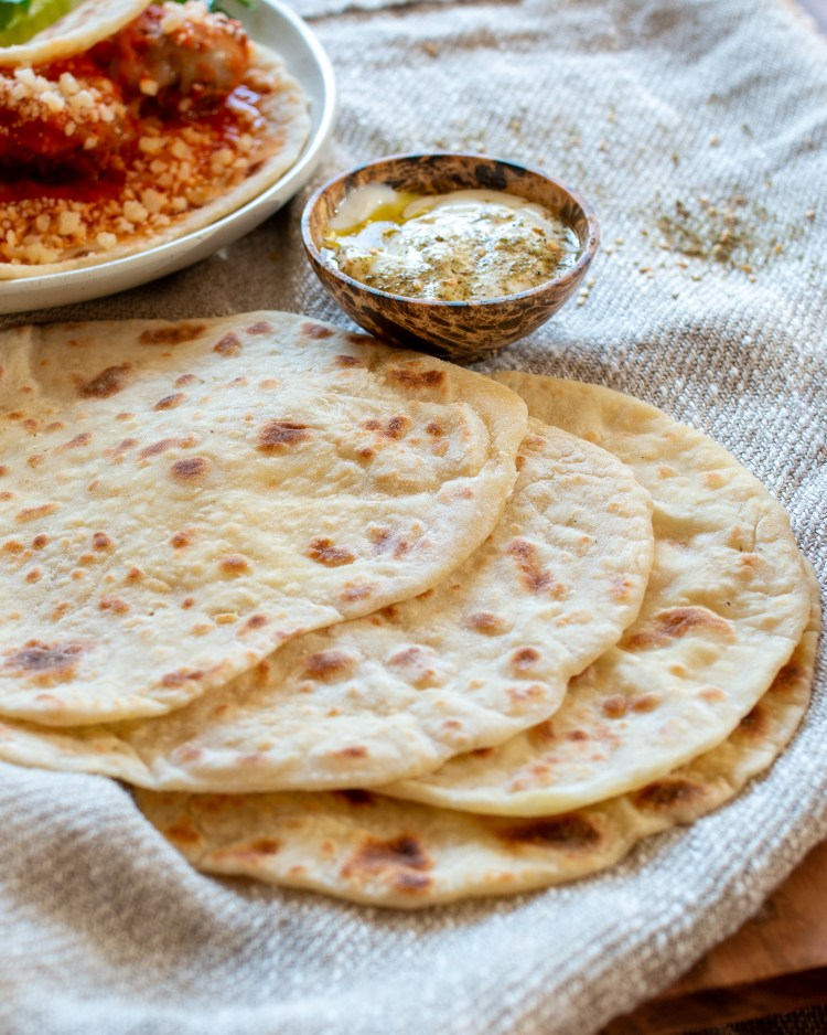 a stack of flatbread on a linen tablecloth with yogurt dip in the background.