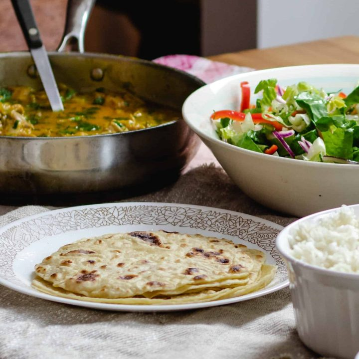 flatbread, curry, and salad laid out on a table.