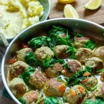 a pan full of brothy turkey meatballs with mashed potatoes and lemons.