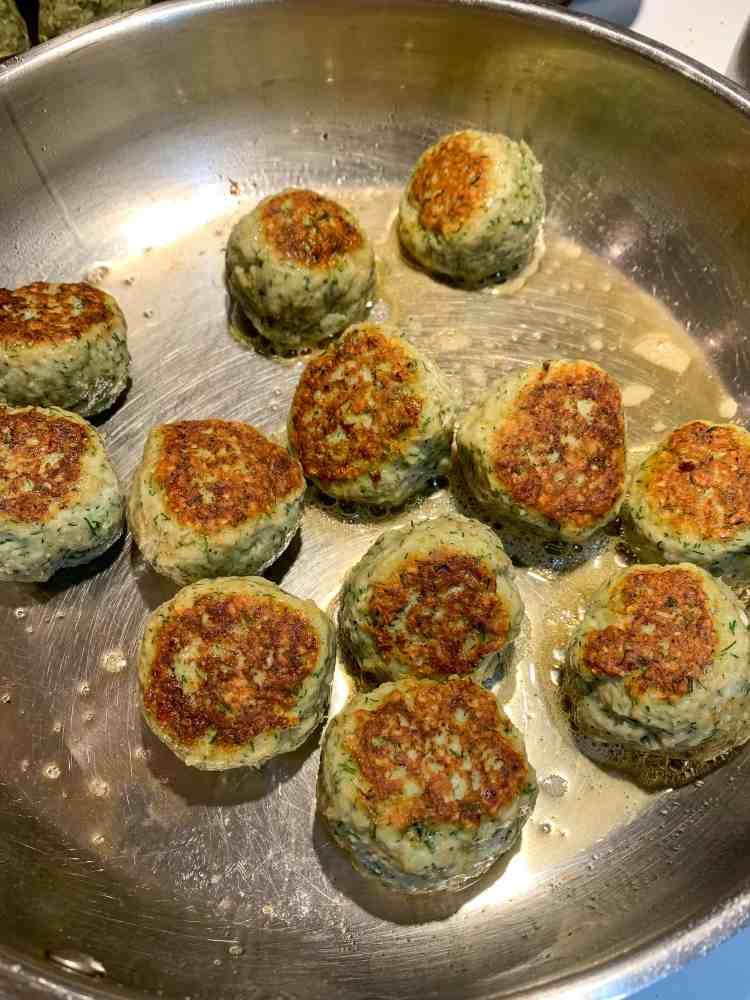 turkey meatballs frying in a pan.