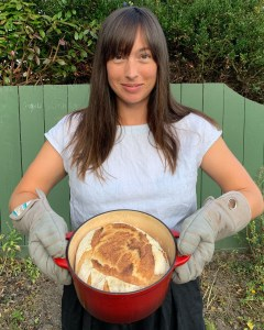 a proud bread baker holding a loaf of bread baked in a Dutch oven.