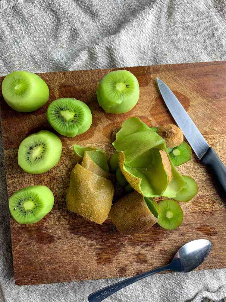 peeled kiwis and their skins on a cutting board.