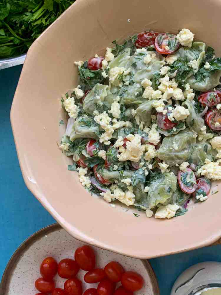 a bowl of tortellini salad on a blue table.