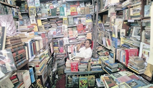 Things To Do in Lima Outside of Miraflores - Man sitting in book shop overflowing with books