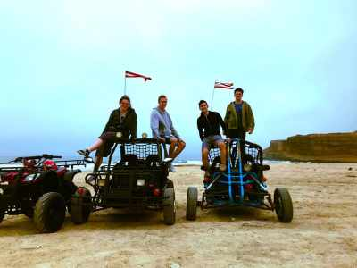 Four of us ATV riding Paracas quad bikes on beach in the Paracas National Reserve with sunset background