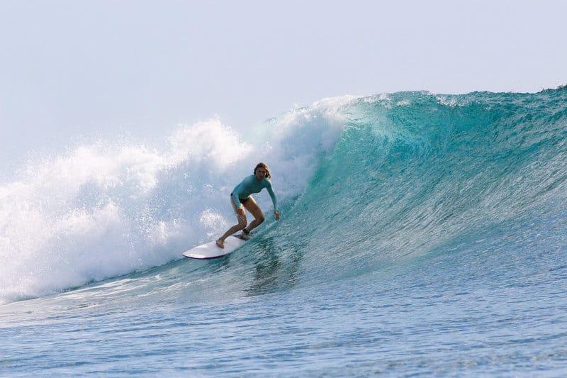 Woman surfing a wave in Mancora Peru surf resort