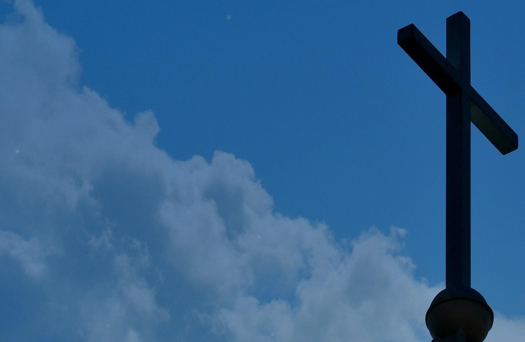 Black cross in a cloudy sky by alan ballou