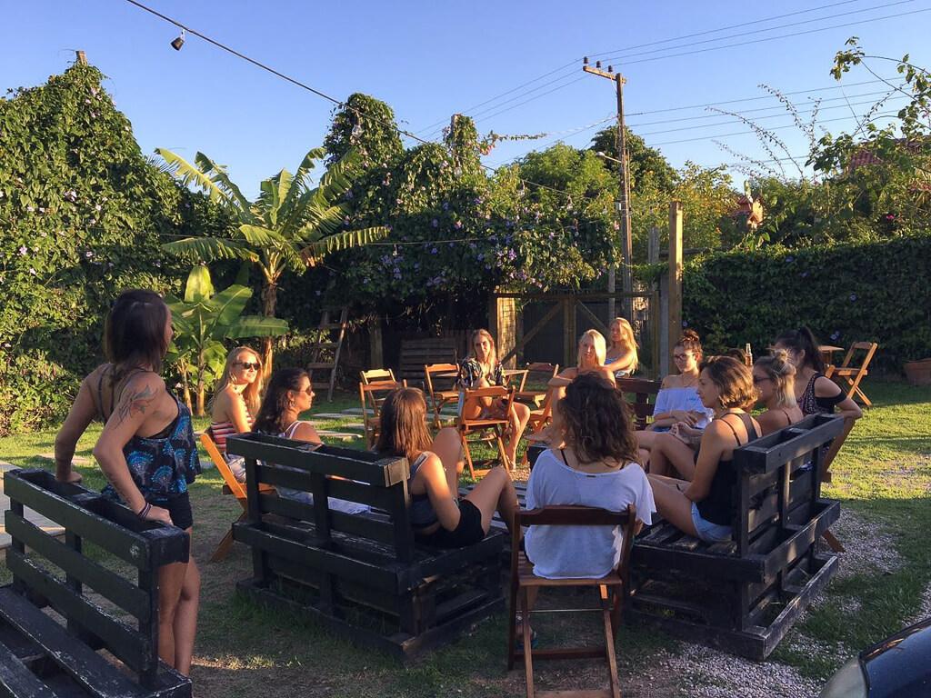 Grupo de pessoas, sentadas ao redor de uma mesa grande de madeira, conversam no fim de tarde na área externa do Innbox Hostel