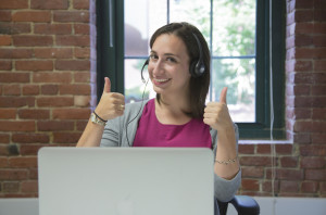 Employee at a laptop and wearing headset