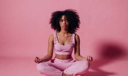 woman in pink crop top and jogging pants practicing yoga