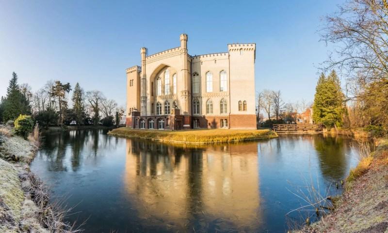 Południowa fasada zamku w Kórniku skąpana w ciepłym świetle wschodzącego słońca. Woda w fosie pokryta cienką warstwą lodu. Budowla neogotycka w stylu gotyku angielskiego.