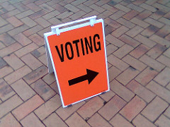 A sign with an arrow and the word Voting