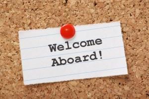 Welcome Aboard! note pinned to a cork notice board